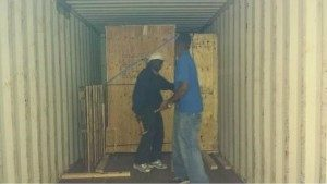 Movers securing crates in storage unit